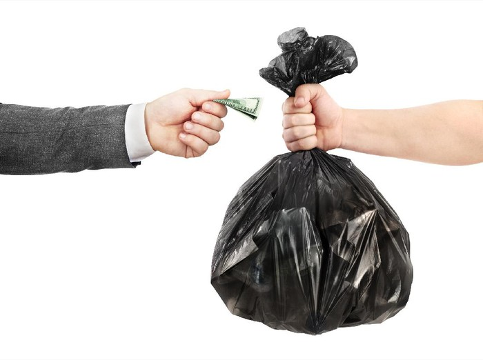 The concept of recycling. A male hand in a jacket transfers money to the other hand in exchange for a garbage bag.