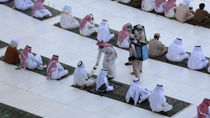 This picture taken early on May 24, 2020 shows a local official handing out bottles of Zamzam water to worshippers gathering in rows before the Kaaba at the Grand Mosque in Saudi Arabias holy city of Mecca to attend the prayers of Eid al-Fitr, the Muslim holiday which starts at the conclusion of the holy fasting month of Ramadan. - Saudi Arabia began a five-day, round-the-clock curfew from May 23 after COVID-19 coronavirus infections more than quadrupled since the start of Ramadan to around 68,000 -- the highest in the Gulf. (Photo by - / AFP)