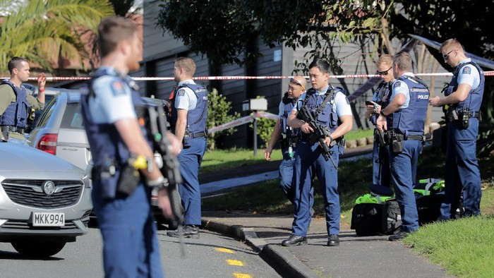 Armed police gather at the scene of a shooting incident following a routine traffic stop in Auckland, New Zealand, Friday, June 19, 2020. New Zealand police say a few officers have been shot and seriously injured and a suspect is on the run. (Michael Craig/New Zealand Herald via AP)