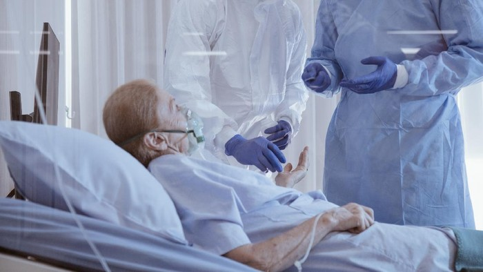 Infected patient on takecare of Doctor and nurse with x-ray Lung in quarantine lying on bed in hospital from coronavirus covid 19 disease. Covid19 or corona virus is world global social issue concept.