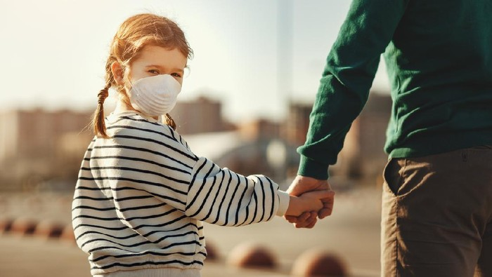 Little boy in medical mask hugging crop mother and looking at camera during coronavirus outbreak against gray background
