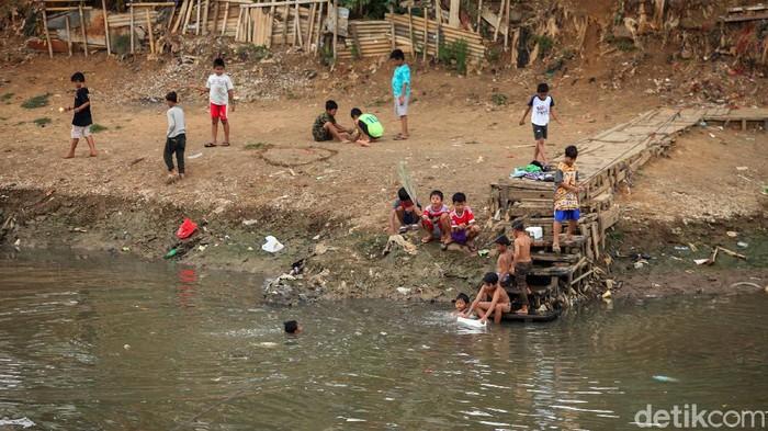 Anak-anak di kawasan Banjir Kanal Barat isi waktu libur dengan bermain di bantaran kali bersama teman-teman. Beberapa diantaranya juga tampak berenang di kali.