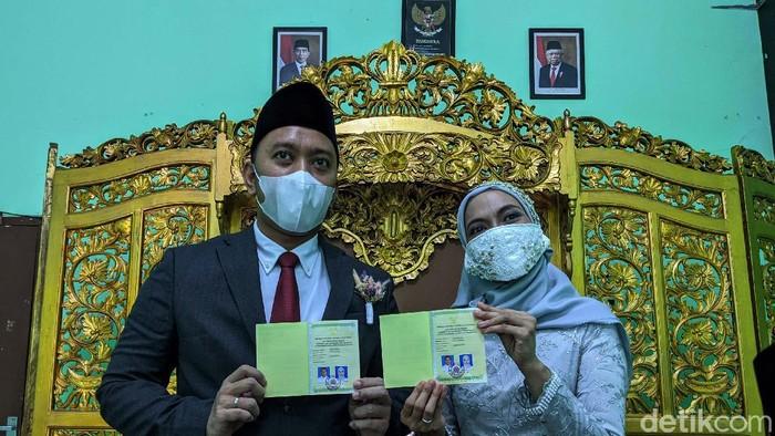 Pasangan pengantin Romdoni dan Dini Larasati menikah di KUA Cimanggis, Depok, Minggu (21/6). Prosesi akad nikah masih menggunakan protokol kesehatan COVID-19.