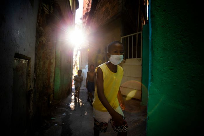 RIO DE JANEIRO, BRAZIL - JUNE 18: Residents of the Tuiuti Community, located in the Benfica neighborhood receive food donations amidst the coronavirus (COVID-19) pandemic on June 18, 2020 in Rio de Janeiro, Brazil. A partnership between the social project Mutirao Presente and the Boxing project