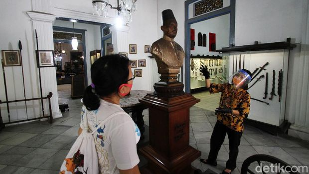 Petugas museum menyambut kedatangan tamu di depan pagar Museum Radya Pustaka di Solo, Jawa Tengah, Selasa (23/6). Museum tertua di Indonesia yang didirikan oleh Kanjeng Raden Adipati Sosrodiningrat IV pada 18 Oktober 1890 ini dibuka pertama kalinya sejak Kondisi Luar Biasa (KLB) diberlakukan  di Solo Maret lalu
