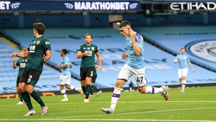 MANCHESTER, ENGLAND - JUNE 22: Phil Foden of Manchester City celebrates after scoring his teams fifth goal during the Premier League match between Manchester City and Burnley FC at Etihad Stadium on June 22, 2020 in Manchester, England. Football stadiums around Europe remain empty due to the Coronavirus Pandemic as Government social distancing laws prohibit fans inside venus resulting in all fixtures being played behind closed doors. (Photo by Michael Regan/Getty Images)