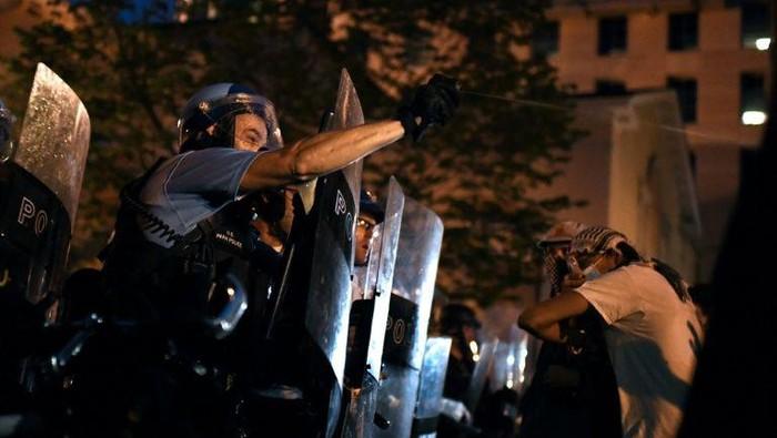 Polisi mencoba menghalangi para demonstran yang ingin merobohkan patung presiden ketujuh AS (AFP Photo)