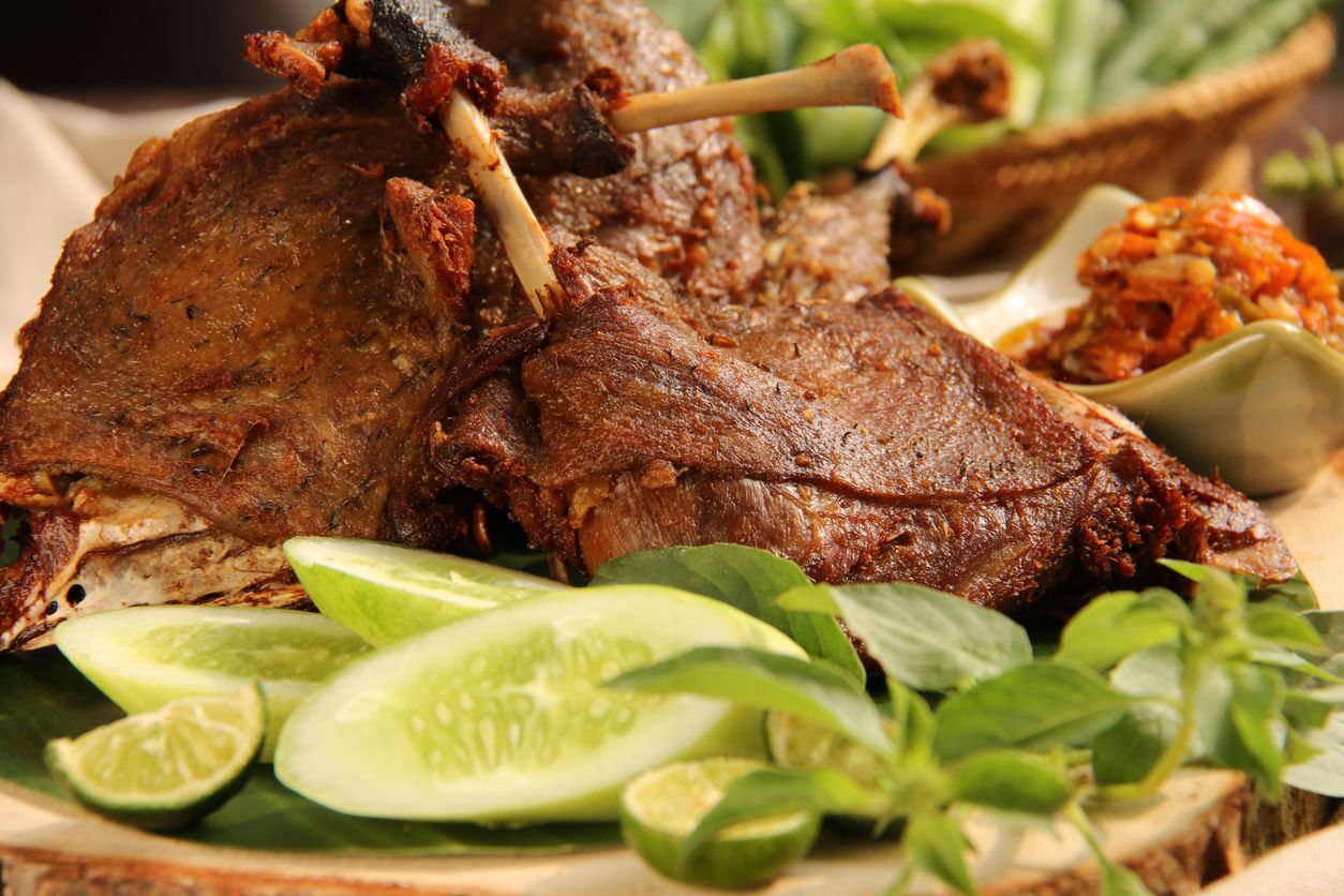 Bebek Goreng, one popular Indonesian poultry dish of deep-fried duck; served with fresh vegetables and chili paste. The duck legs are arranged on a natural wooden serving board that has been lined with banana leaf.