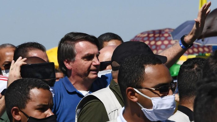 Brazilian President Jair Bolsonaro (C) greets supporters during a demonstration in Brasilia, on May 31, 2020 during the COVID-19 novel coronavirus pandemic. - Bolsonaro, who fears the economic fallout from stay-at-home orders will be worse than the virus, has berated governors and mayors for imposing what he calls