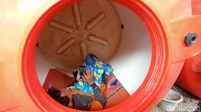 Salah satu relawan pemulasaraan jenazah, Kristanto (39) saat tiduran di tangki air di kantor BPBD Kudus, Rabu (24/6/2020).