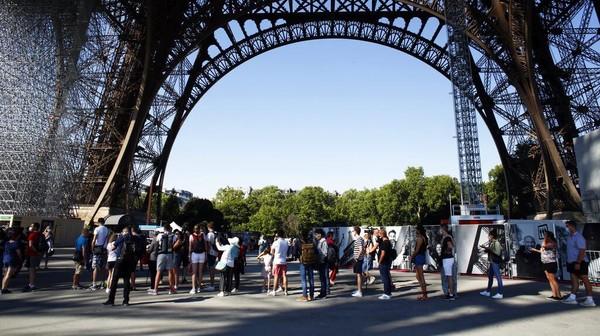 Sejumlah pengunjung mengantre untuk memasuki Menara Eiffel yang kembali dibuka untuk umum, Kamis (25/6/2020).
