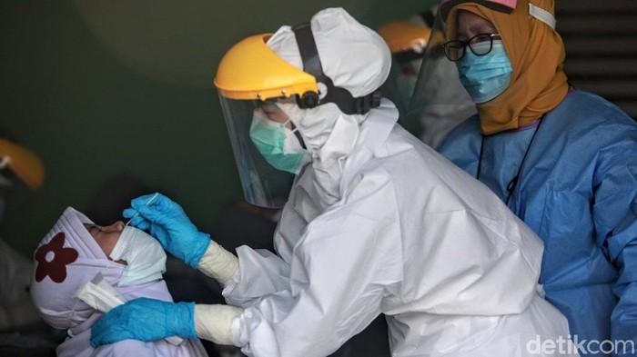 Petugas melakukan tes swab Corona di Pasar Sayur Cipulir, Jaksel, Kamis (25/6). Tes tersebut sebagai upaya untuk mengetahui persebaran virus Corona di daerah tersebut.