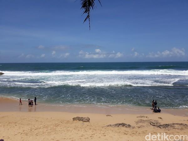 Tampak beberapa wisatawan tengah bersantai di pinggir pantai dengan menggunakan masker dan beberapa wisatawan lainnya tampak asyik bermain air.