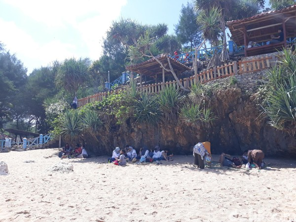 Wisatawan di Pantai Kukup berjejer di bawah tebing. Mereka menjaga jarak antara kelompok yang satu dengan lainnya.