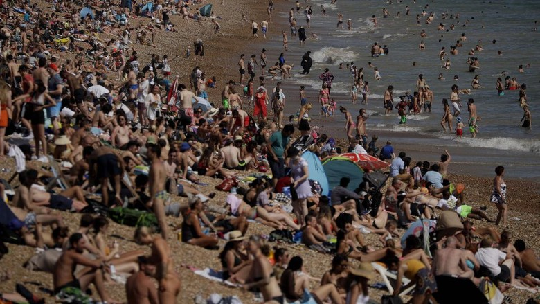 On Britains hottest day of the year so far with temperatures reaching 32.6 degrees at Heathrow, people relax in the sea and on Brighton Beach in Brighton, England, Wednesday, June 24, 2020. The British government announced Tuesday that from July 4 social-distancing rules will be relaxed. People will be advised to stay at least 1 meter (3 feet) apart from others, rather than requiring 2 meters -- as long as they take other measures to reduce transmission of the virus, such as wearing a mask in enclosed spaces. (AP Photo/Matt Dunham)