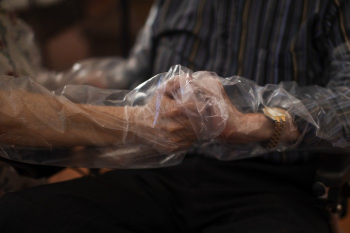 In this Monday, June 22, 2020 photo, Agustina Cañamero, 81, and Pascual Pérez, 84, hug and kiss through a plastic film screen to avoid contracting the new coronavirus at a nursing home in Barcelona, Spain. Even when it comes wrapped in plastic, a hug can convey tenderness and relief, love and devotion. The fear that gripped Agustina Cañamero during the 102 days she and her 84-year-old husband spent physically separated during Spains coronavirus outbreak dissolved the moment the couple embraced through a screen of plastic film. (AP Photo/Emilio Morenatti)