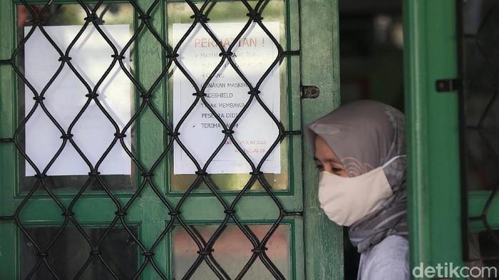 Guru membagikan laporan hasil belajar (rapor) kenaikan kelas kepada wali murid di SD Negeri Menteng 01, Jakarta, Kamis (25/6/2020). Pembagian rapor akhir tahun pelajaran 2019/2020 dilaksanakan mengikuti protokol kesehatan pencegahan penularan COVID-19 dengan menjaga jarak, mengenakan masker, pengukuran suhu tubuh serta melakukan pembagian rapor secara bertahap dari 24-26 Juni 2020.