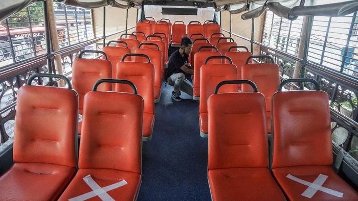 Petugas Dinas Perhubungan menempelkan tanda jaga jarak (physical distancing) di kursi bus tingkat wisata di kantor Dinas Perhubungan, Solo, Jawa Tengah, Jumat (26/6/2020). Bus tingkat wisata keliling Kota Solo akan mulai dioperasikan kembali pada 27 Juni 2020 sesuai tatanan normal baru dengan menerapkan protokol kesehatan seperti wajib mengenakan masker, menjaga jarak dan mencuci tangan. ANTARA FOTO/Mohammad Ayudha/wsj.