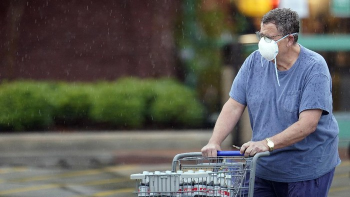A shopper wears a mask as he pushes a grocery cart in the rain Thursday, June 25, 2020, in Houston. Texas Gov. Greg Abbott said Wednesday that the state is facing a massive outbreak in the coronavirus pandemic and that some new local restrictions may be needed to protect hospital space for new patients. (AP Photo/David J. Phillip)