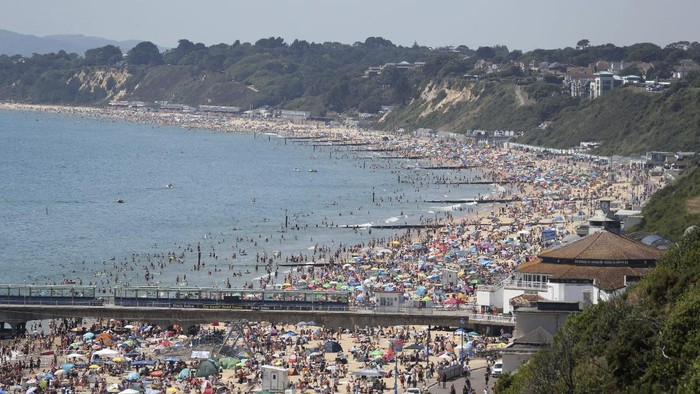Crowds gather as hot weather draws crowds to the beach in Bournemouth, England, Thursday June 25, 2020. Coronavirus lockdown restrictions are being relaxed but people should still respect the distancing requirements between family groups. According to weather forecasters this could be the UKs hottest day of the year, so far, with scorching temperatures forecast to rise even further. (Andrew Matthews/PA via AP)