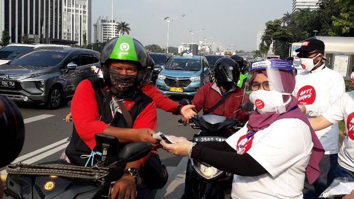 Wakil Ketua KPK Lili Pintauli Siregar membagi-bagikan masker ke pengendara yang melintas di Jalan Jenderal Sudirman, Jakarta Pusat, Jumat (26/6/2020).