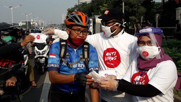 Wakil Ketua KPK Lili Pintauli Siregar membagi-bagikan masker ke pengendara yang melintas di Jalan Sudirman, Jakarta Pusat, Jumat (26/6/2020).