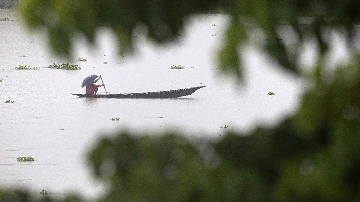 Villagers row country boats through floodwaters in Morigaon district of Assam, India, Friday, June 26, 2020. Following incessant rainfall, the Brahmaputra river and its tributaries continued to rise flooding several districts in the state. (AP Photo/Anupam Nath)