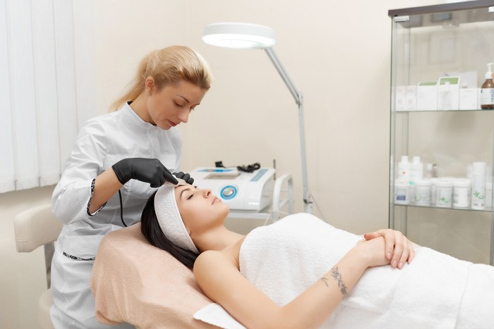 Hardware cosmetology. Cosmetologist doing procedure of ultrasonic cleaning of face. Young woman getting ultrasonic peeling in beauty salon. Cosmetological clinic. Healthcare, clinic, cosmetology