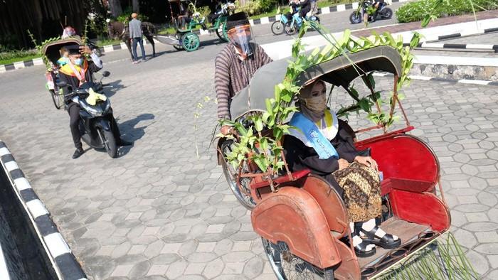 Perwakilan wisudawan Universitas Sebelas Maret (UNS) mengendarai transportasi ramah lingkungan saat mengikuti prosesi acara Wisuda Luring dan Daring secara Drive Thru di kampus setempat, Solo, Jawa Tengah, Sabtu (27/6/2020). Wisuda dengan konsep drive thru tersebut digelar UNS sebagai bentuk kreatifitas adaptasi kampus setempat dalam situasi normal baru ditengah Pandemi COVID-19. ANTARA FOTO/Maulana Surya/hp.