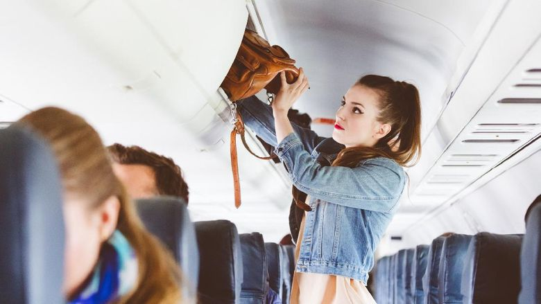 Female passenger storing handbag in overhead locker in airplane. Young woman in the cabin storing hand luggage in the overhead locker.