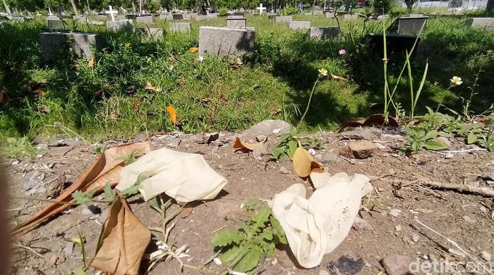 APD tenaga medis bekas penanganan jenazah COVID-19 berserakan di TPU Babat Jerawat, Surabaya. Mulai dari hazmat, sarung tangan dan face shield.