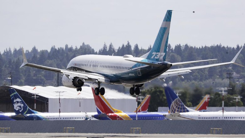 A Boeing 737 MAX jet heads to a landing and past grounded 737 MAX jets behind at Boeing Field following a test flight Monday, June 29, 2020, in Seattle. The jet took off from Boeing Field earlier in the day, the start of three days of re-certification test flights that mark a step toward returning the aircraft to passenger service. The Federal Aviation Administration test flights over the next three days will evaluate Boeings proposed changes to the automated flight control system on the MAX, a system that activated erroneously on two flights that crashed, killing 346 people. (AP Photo/Elaine Thompson)