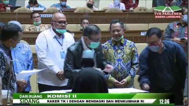Mendagri Tito Karnavian dan Menkum HAM Yasonna Laoly saat penandatanganan persetujuan RUU Pilkada Serentak di Komisi II DPR