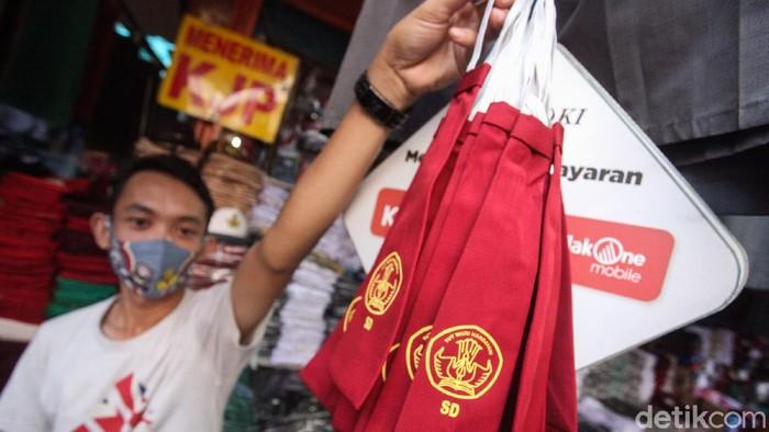 Penjualan seragam sekolah ikut terdampak pandemi Corona. Bahkan, omzet para pedagang berkurang hingga 70 persen.