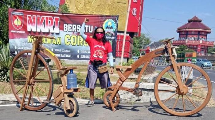 Sarijo berpose dengan sepeda kayunya di jalan Yogya-Solo, tugu batas Klaten-Sukoharjo, Minggu (28/6/2020).