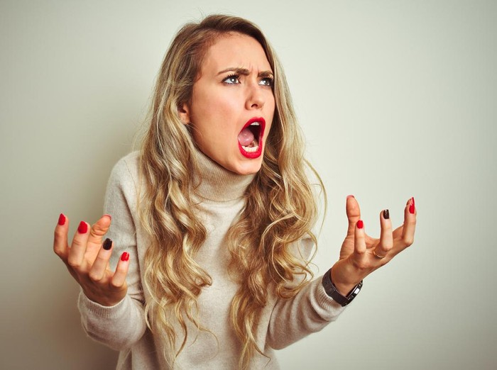 Beautiful woman wearing winter turtleneck sweater over isolated white background crazy and mad shouting and yelling with aggressive expression and arms raised. Frustration concept.