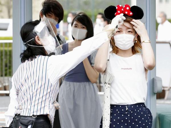 Taman hiburan yang populer di kawasan Tokyo tersebut kembali dibuka untuk umum dengan menerapkan sejumlah protokol kesehatan. Para pengunjung yang hendak masuk area taman hiburan Disneyland Tokyo tampak diukut suhu tubuhnya oleh petugas. Kyodo News via AP Photo.