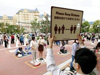 Selain itu, para pengunjung juga diimbau untuk menerapkan physical distancing atau jaga jarak saat beraktivitas di taman hiburan tersebut. Kyodo News via AP Photo.