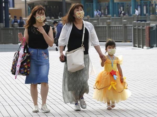Para pengunjung juga diwajibkan untuk memakai masker saat menikmati atraksi di kawasan taman hiburan tersebut. Selain itu, karakter-karakter di Disneyland dan Disneysea itu tak bisa berbaur dengan pengunjung. Micky Mouse dan dan Minnie Mouse akan menjaga jarak. Kyodo News via AP Photo.