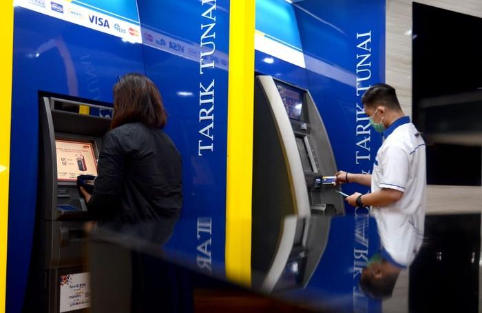 """Nasabah sedang mengambil uang di mesin ATM milik PT Bank Tabungan Negara (Persero) Tbk., di Jakarta, Rabu (1/7). ATM Bank BTN menyabet predikat layanan paling prima dari survey """"Bank Service Excellence Monitor (BSEM)"""". Dari penyelenggaraan survei BESM ke-24, bank yang dinahkodai Pahala N. Mansury sebagai direktur utama BTN tersebut mencatatkan skor layanan ATM tertinggi yakni 89,66%. Angka tersebut naik signifikan dibanding survei pada tahun sebelumnya sebesar 86,10%."""
