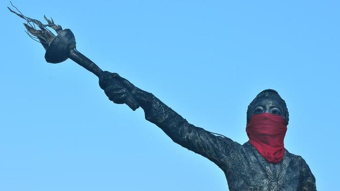 Patung Raden Ajeng Kartini dipasangi masker di Jepara, Jawa Tengah, Rabu (1/7/2020). Patung yang menjadi simbol kota Jepara tersebut dipasangi masker guna mensosialisasikan pada warga untuk meningkatkan kesadaran mengenakan masker menyusul lonjakan tajam kasus terkonfirmasi positif COVID-19 di wilayah itu dari yang semula lima kasus menjadi 398 kasus positif dalam waktu lima pekan dan 27 diantaranya meninggal. ANTARA FOTO/Yusuf Nugroho/aww.