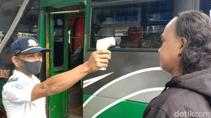 Petugas memeriksa suhu tubuh penumpang bus