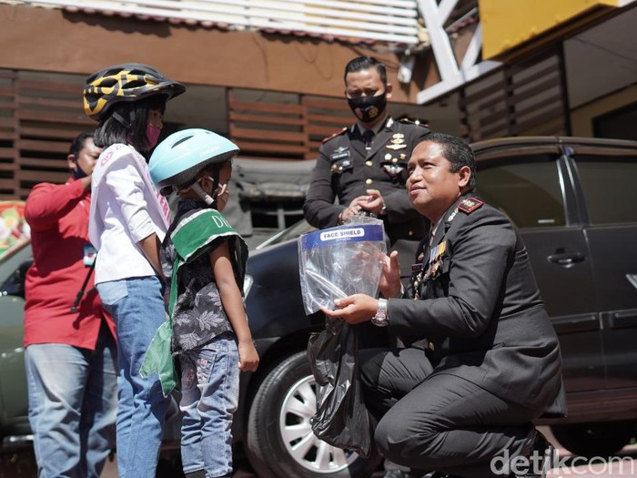 Kakak beradik di Kota Probolinggo bersepeda menuju mapolres. Mereka memberi kado face shield dan masker ke polisi di HUT ke-74 Bhayangkara.