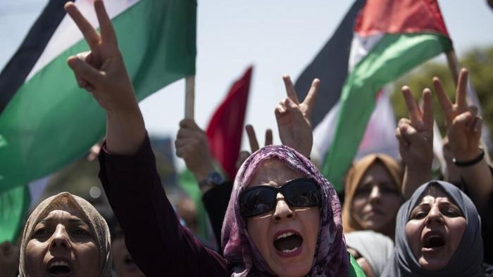 Sejumlah warga Palestina turun ke jalan untuk tolak rencana aneksasi Israel di Tepi Barat. Dalam aksi itu demonstran membawa poster hingga bendera Palestina.