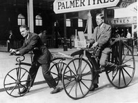 Two men (L-R) ride on early bicycles. The Hobby Horse was invented by Karl Von Drais in 1818. In 1863, a French coachbuilder added cranks and pedals and invented the boneshaker, circa 19th century.