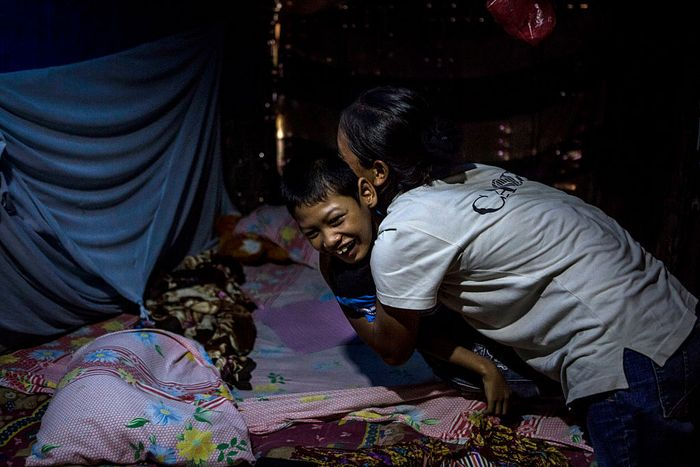 JAMBON, PONOROGO, INDONESIA - MARCH 25:  Jamila, 13, who suffers from Down syndrome, lies on a floor mat inside a house at Sidowayah Village in Jambon subdistrict on March 25, 2016 in Ponorogo district, Indonesia. Jamila has been paralyzed and mute since she was a baby and is now being cared for by grandmother of her parents as his mother worked as a migrant worker in Malaysia. More than 400 people suffer from psychosocial disabilities in Ponorogo, East Java, where villagers and government officials blamed incest, malnutrition and iodine deficiency as the cause for the illness. In villages such as Sidoharjo, Karangpatihan and Krebet, both adolescents and adults suffer from severe physical retardation, also known as