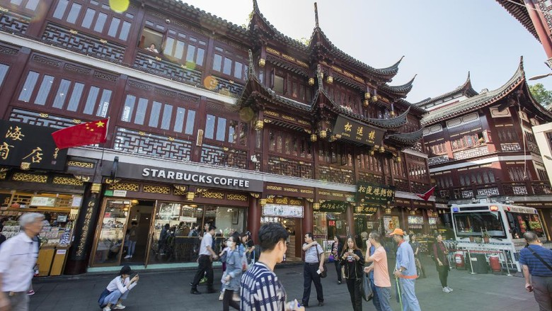 Inside Yu garden, Shanghai, China. Starbucks coffee shop among other food and drink stores in the traditional style buildings. A lot tourists in the front of the building.