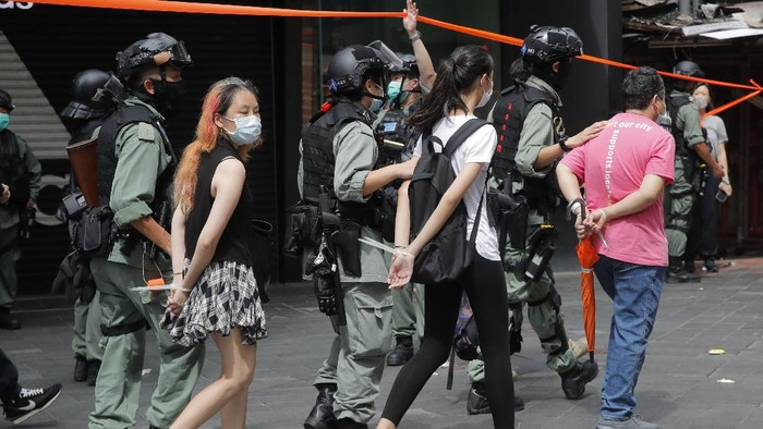 Police detain protesters after a protest in Causeway Bay before the annual handover march in Hong Kong, Wednesday, July. 1, 2020. Hong Kong marked the 23rd anniversary of its handover to China in 1997, and just one day after China enacted a national security law that cracks down on protests in the territory. Hong Kong police said on Facebook they had arrested over 30 people on various charges, from unlawful assembly to the violation of a national security law on the first day of the law. (AP Photo/Kin Cheung)