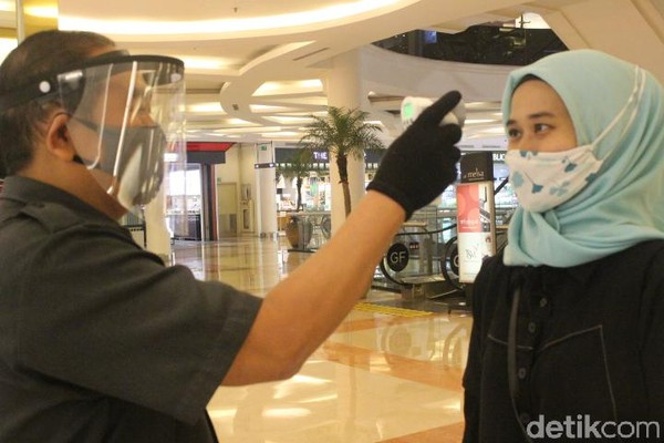 Di Metro Department Store, TSM Bandung, setiap pengunjung yang akan masuk juga wajib dicek kembali suhu tubuhnya. (Foto: Putu Intan/detikcom)