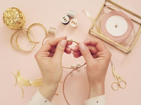 Jewelry designer workplace. Woman hands making handmade jewelry. Freelance fashion femininity workspace in flat lay style. Pastel pink and gold